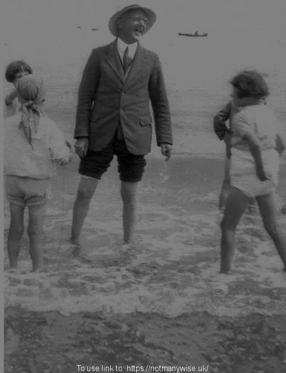 1936 Rev Haydon paddling in the sea with some children.