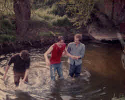 Baptism meaning: one way is in a river (Peter Reason on the right!)