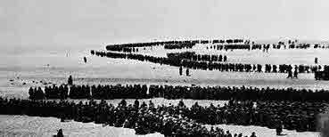Escaping soldiers lined up on the beach at Dunkirk.