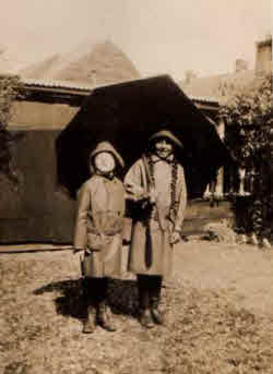 Two girls from John's family standing under an umbrella. Earith flooding.