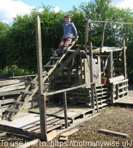 A lad building a house out of pallets.