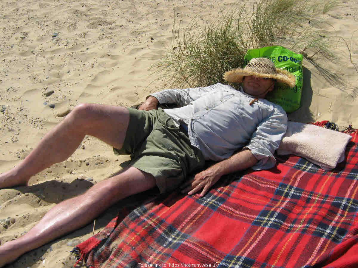 Stress free lying on a beach relaxing and snoozing.