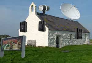 A Techie church with outside speakers, satellite dish, large screen and strobe light .