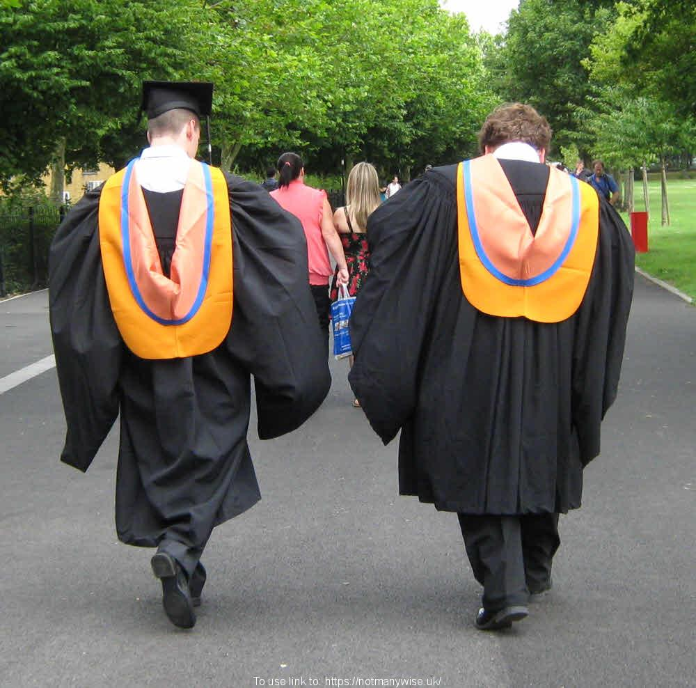 Two university students walking on Graduation day in their gowns.